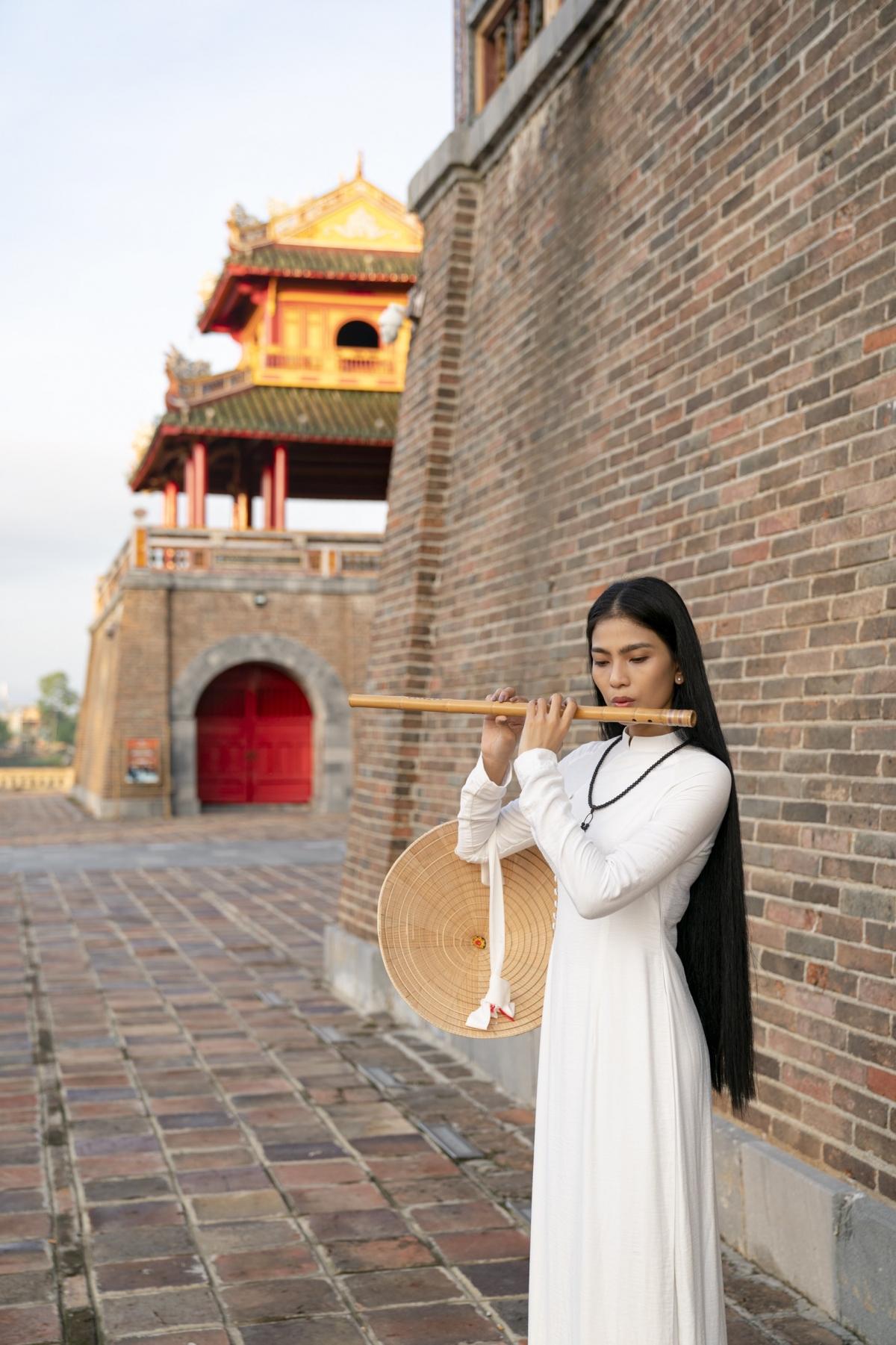 Diện bộ áo dài trắng tự may, cổ đeo tràng hạt, đầu đội nón lá, tay cầm cây sáo thổi..., Trương Thị May được nhiếp ảnh gia nổi tiếng Trịnh Quốc Huy ghi lại những khoảnh khắc dung dị, hoài cổ tại đất cố đô.