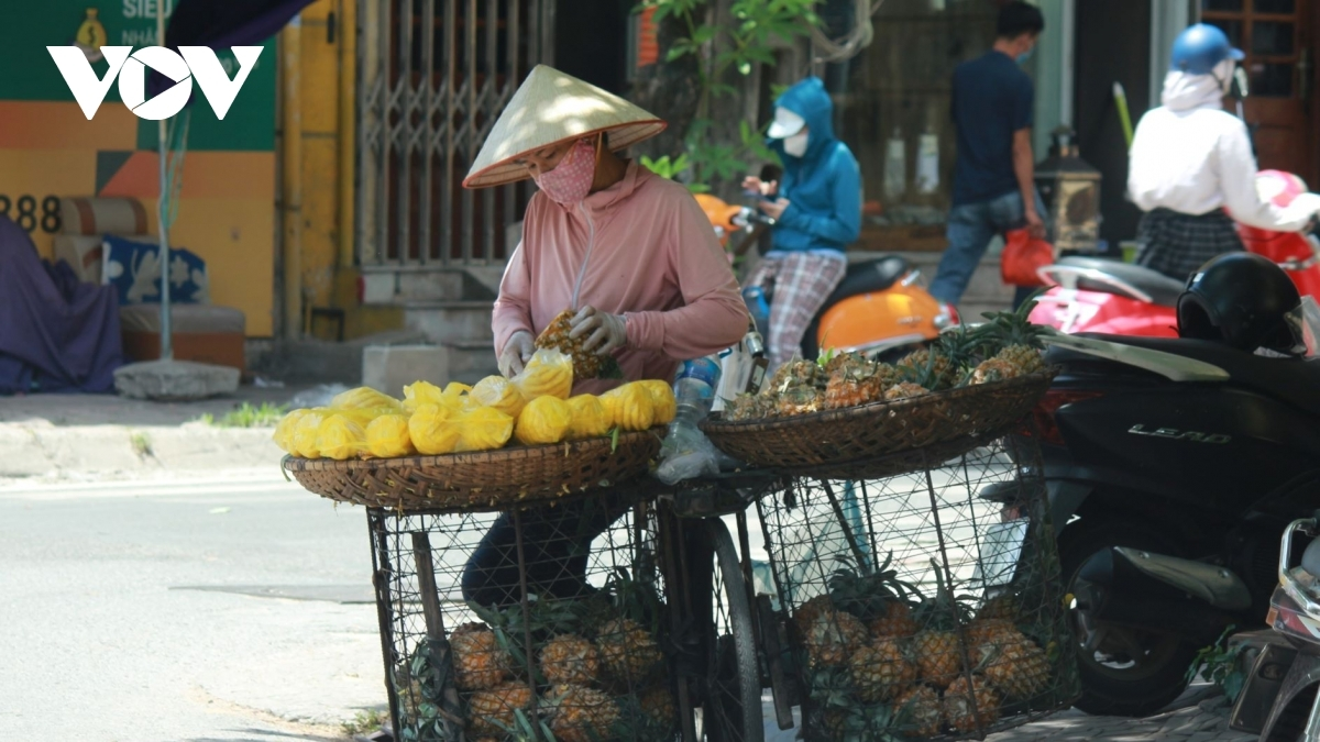 Street vendors, in protective clothing, have no choice but to go out and sell products to make ends meet.