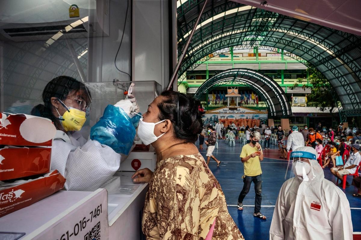 Một người phụ nữ ở khu Khlong Toey lấy dịch mũi xét nghiệm SARS-CoV-2. Ảnh: New York Times