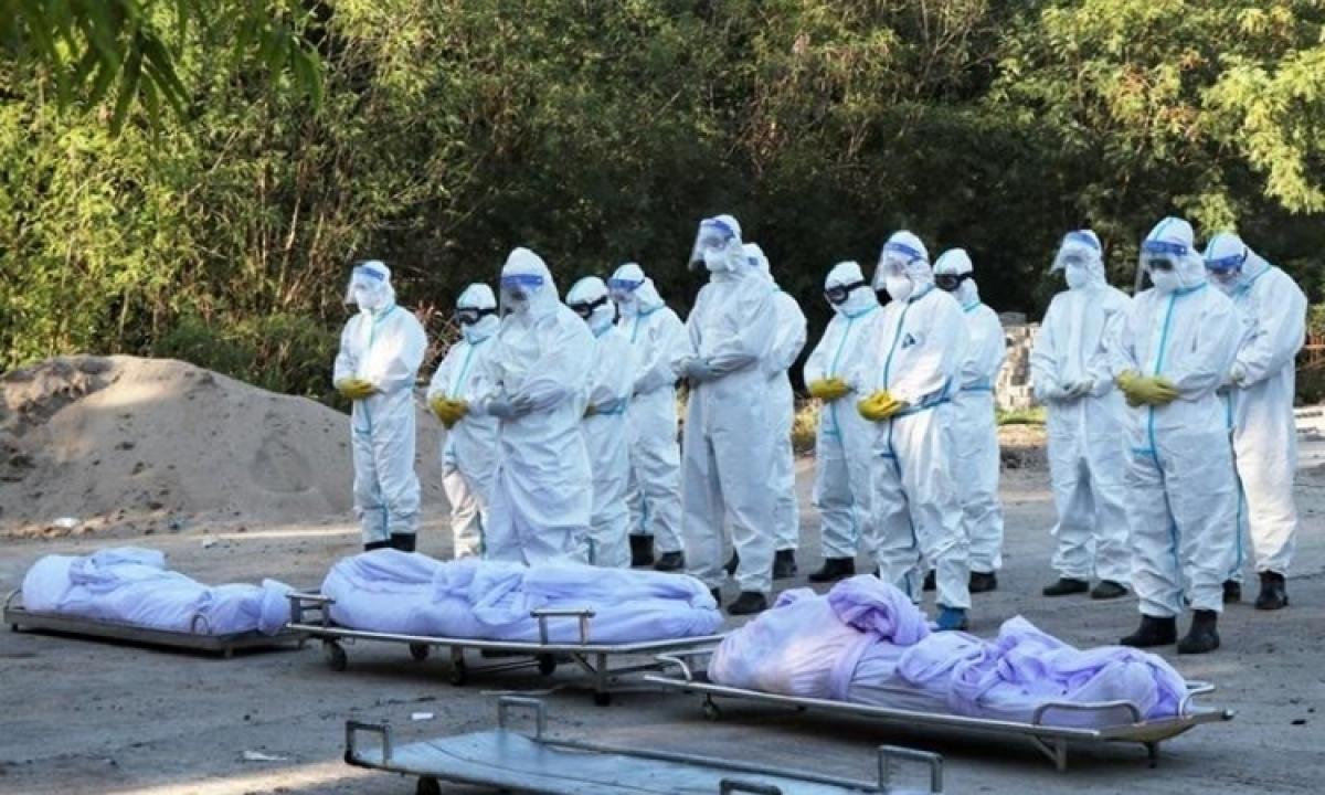 Nhân viên tình nguyện chuẩn bị an táng thi thể bệnh nhân Covid-19 tại một nghĩa trang ở Mandalay, Myanmar, hôm 14/7. Ảnh: Reuters