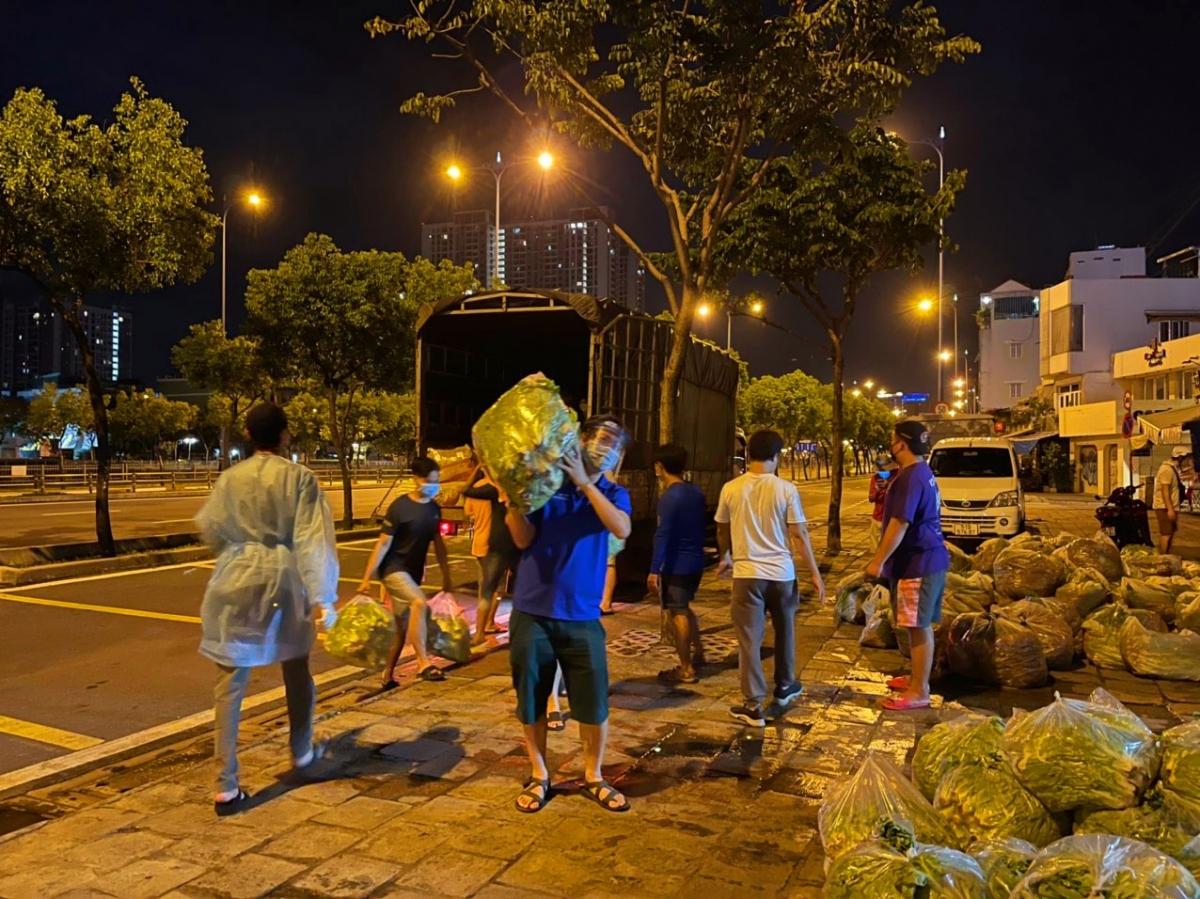 """Chia sẻ những khó khăn, vất vả đến các lực lượng trực chiến ở tuyến đầu chống dịch và người dân thành phố mang tên Bác, với mong muốn dịch bệnh sớm được kiểm soát, đẩy lùi ở TP.HCM để cuộc sống bình yên sẽ quay trở lại, đại diện Hiệp hội Doanh nhân và Đầu tư Việt Nam – Hàn Quốc (VKBIA) và nhóm thiện nguyện thành viên là """"Saigon Share"""" đã tiếp tục thực hiện """"những chuyến xe nghĩa tình"""" hướng về TP.HCM. (Trong ảnh: Các tình nguyện viên bốc dỡ 13 tấn rau củ chuyển từ Lâm Đồng đến điểm tập kết ở TP.HCM ngày 26/7)"""