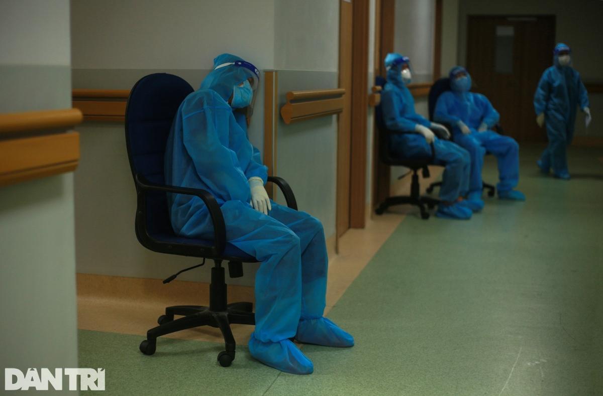 Một số nhân viên y tế khác thấm mệt sau nhiều giờ làm việc căng thẳng, dựa tạm vào tường để nghỉ ngơi trong chốc lát.