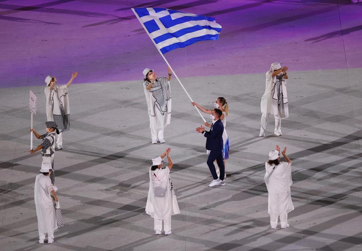 Hai VĐV Eleftherios Petrounias và Anna Korakaki của Hy Lạp cầm cờ tại lễ diễu hành. (Ảnh: Reuters).
