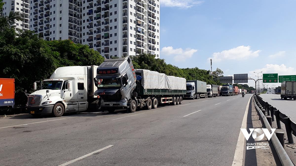 Hàng dài xe tải, container chờ cấp thẻ nhận diện luồng xanh để được đi qua chốt kiểm dịch.