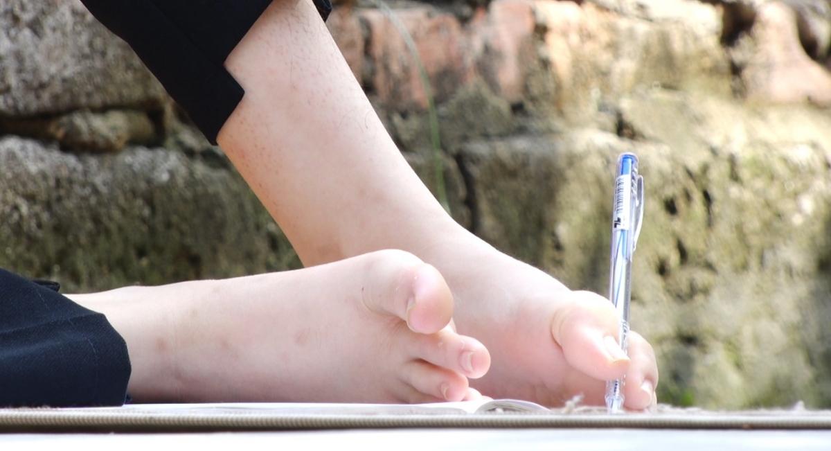Thắm viết bằng chân.