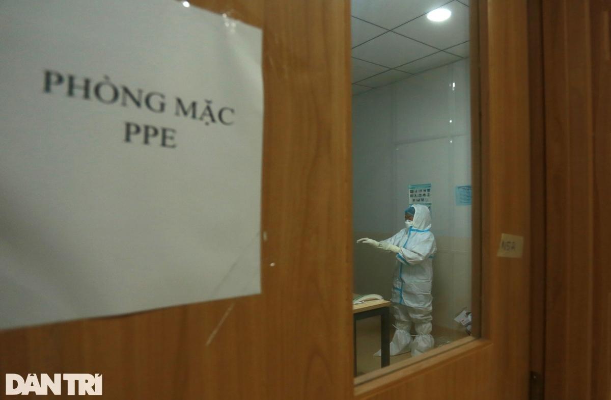 Đúng 21h đêm, 15 y bác sĩ của khu vực điều trị bệnh nhân nặng và nguy kịch hoàn tất việc trang bị đồ bảo hộ ở phòng mặc PPE. Sẵn sàng vào thay ca cho đồng nghiệp.