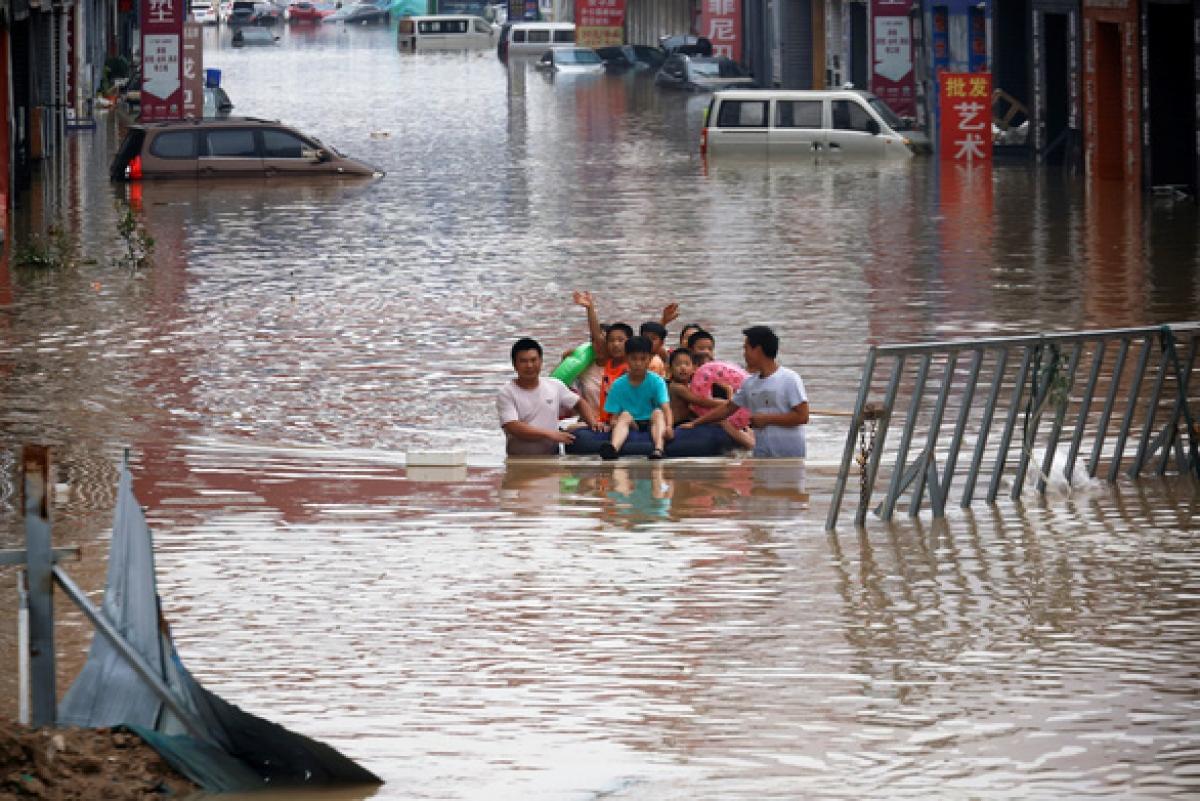 Trẻ em được đưa ra khỏi một con đường bị ngập nước sau mưa lớn ở thành phố Trịnh Châu, tỉnh Hà Nam, miền trung Trung Quốc ngày 22/7. Ảnh: Reuters
