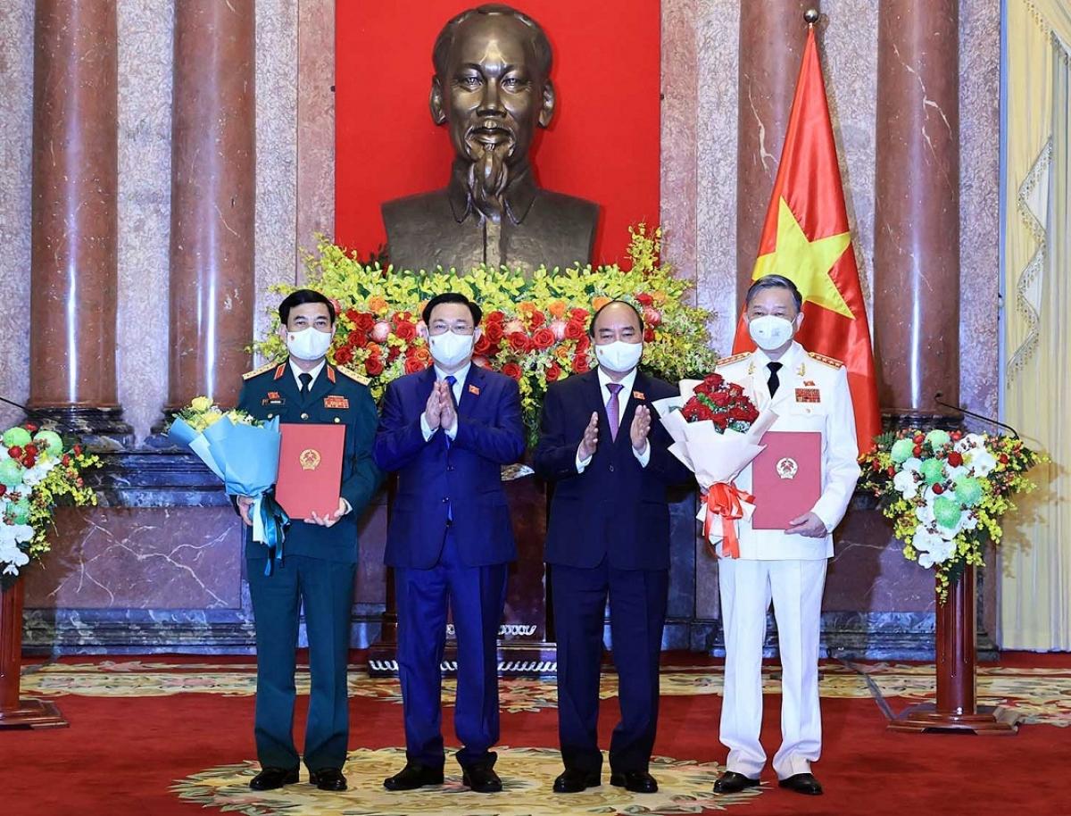 Chủ tịch nước Nguyễn Xuân Phúc trao Quyết định, Chủ tịch Quốc hội Vương Đình Huệ tặng hoa cho Bộ trưởng Bộ Công An, Đại tướng Tô Lâm và Bộ trưởng Bộ Quốc phòng, Đại tướng Phan Văn Giang.