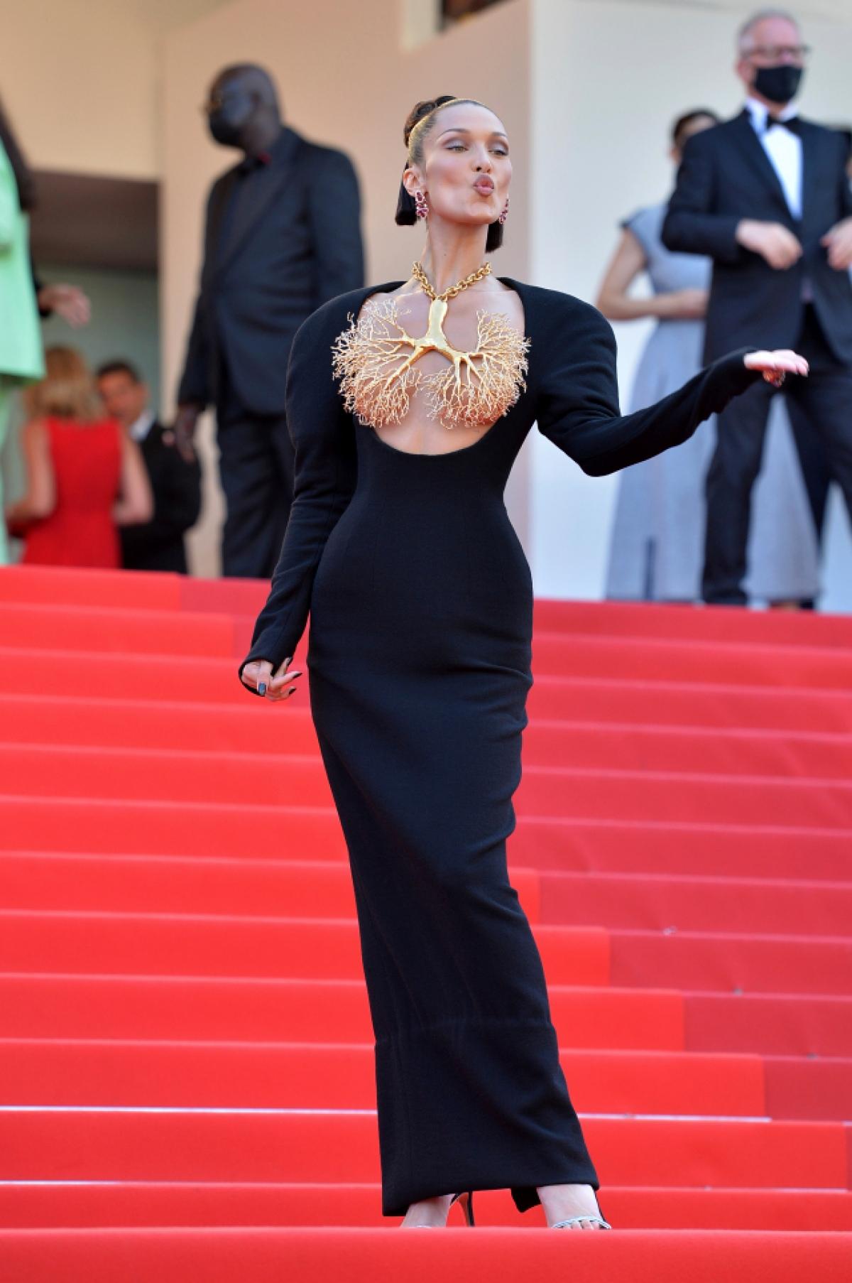 """BellaHadid từ lâu đã trở thành gương mặt quan trọng của Liên hoan phim Cannes. Cô là tâm điểm chú ý khixuất hiện trên thảm đỏ ngày 11/7 khi dự ra mắt phim """"Three floors"""" của đạo diễn Nanni Moretti. Cô diện váy đenkhoét ngực củaSchiaparelli và đeo sợi dây chuyền vàng có mặt là hình lá phổi ôm ngực từ bộ sưu tập thời trang cao cấp mùa thu 2021 của nhà thiết kế."""