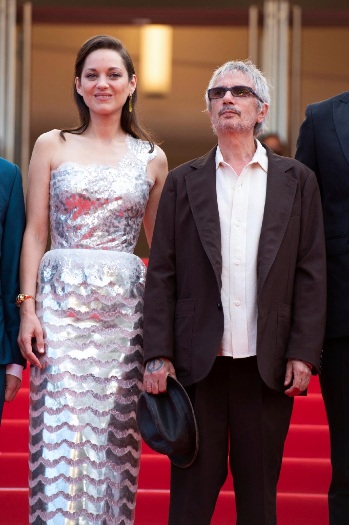 """Là đại sứ lâu năm của Chanel, Marion Cotillard luôn lựa chọn trang phục của nhà mốt Pháp trong các sự kiện. Vào đêm mở màn cho bộ phim """"Annette"""" của mình, nữ diễn viên từng đoạt giải Oscar nổi bật trong thiết kế đầm màu bạc ánh kim từ bộ sưu tập thời trang cao cấp mùa thu 2020 của Chanel. Chiếc váy ghi điểm với chi tiết vai bất đối xứng và chân váy xếp tầng."""