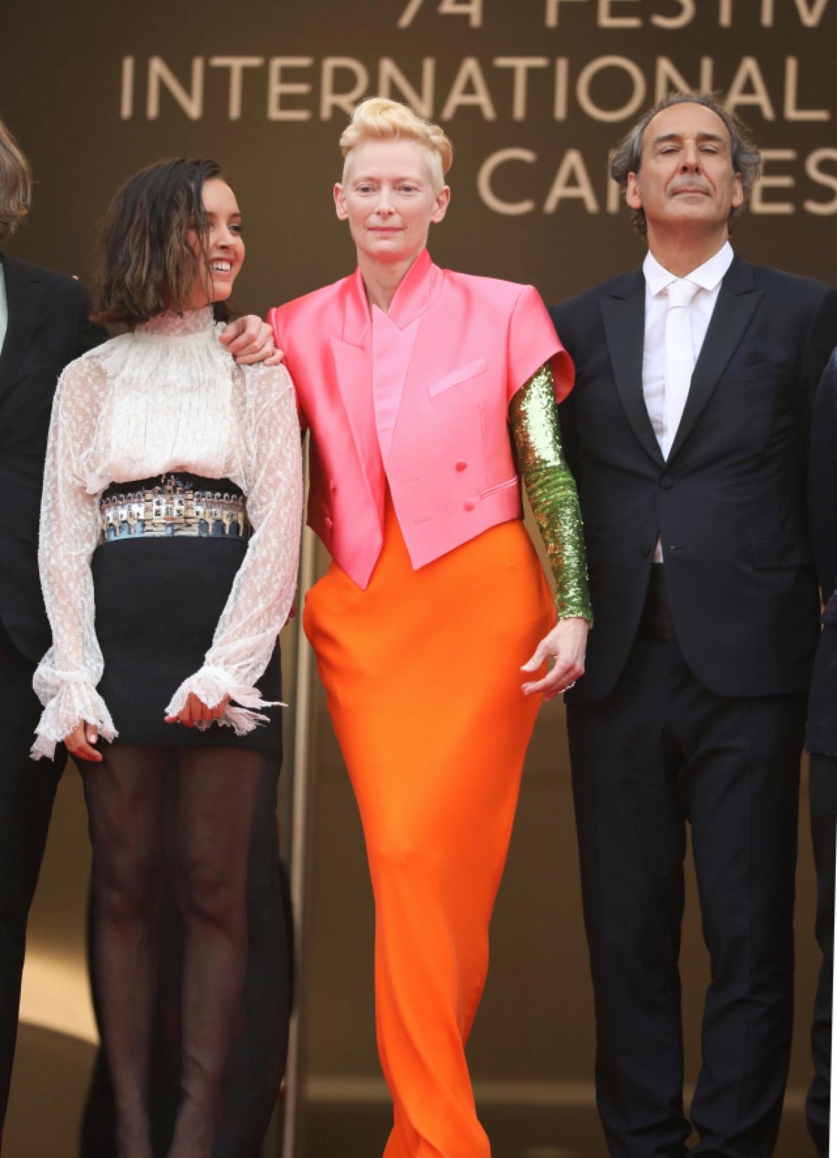 """Minh tinh Tilda Swinton tham dự buổi ra mắt phim """"The French Dispatch"""" vào ngày 12/7 trong một diện mạo bắt mắt của Haider Ackermann. Nữ diễn viên nổi bật với áo blazer màu hồng bolero được cắt cúp và kết hợpvới chân váy màu cam và áo sơ mi dài tay đính sequin màu xanh lá."""