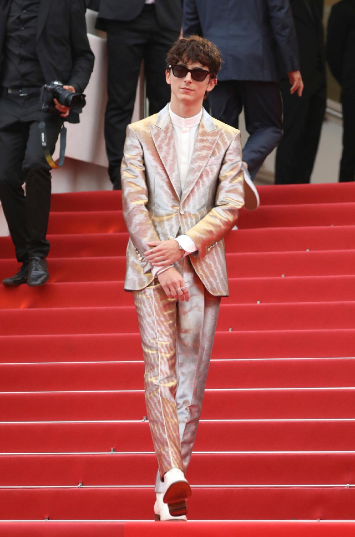 """Timothée Chalamet nhận được nhiều sự chú ý kể từ khi anh được đề cử giải thưởng Oscar vào năm 2017. Xuất hiện lần đầu tiên Liên hoan phim Cannes vào ngày 12/7 tại buổi ra mắt bộ phim """"The French Dispatch"""", Chalamet diện bộ vest Tom Ford màu bạc và vàng ánh kim kết hợp với giày bốt và kính râm đen."""