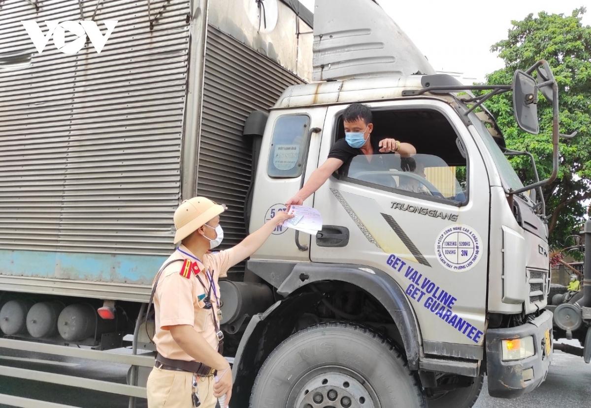 """Lực lượng CSGT kiểm tra giấy tờ chủ phương tiện vận tải """"luồng xanh""""."""