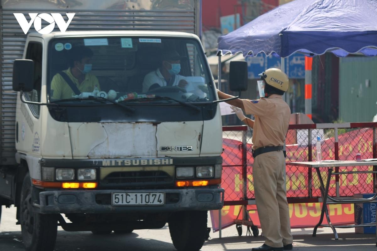 Cảnh sát giao thông kiểm tra giấy tờ của một phương tiện chở hàng hóa ngay tại chốt kiểm soát dịch COVID-19.