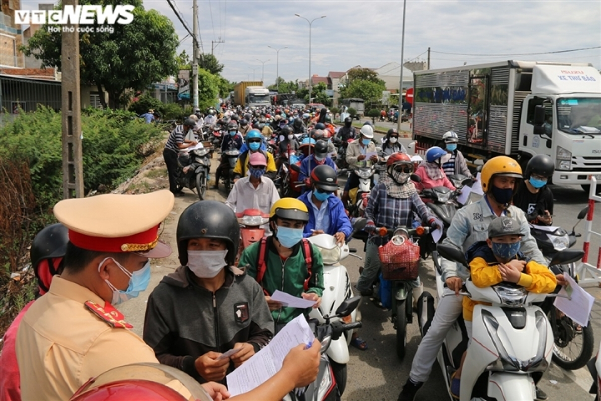 People form a long line on the road which connects Da Nang city to Quang Nam province.
