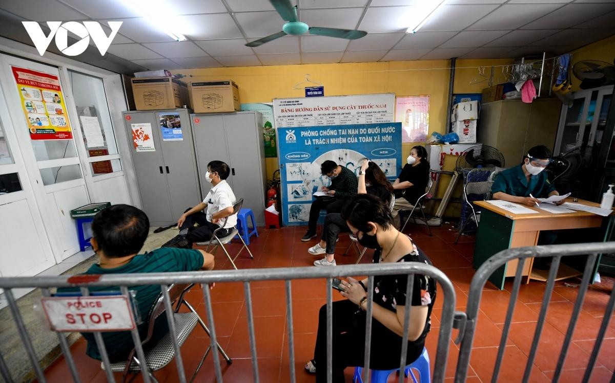 Sau khi làm các thủ tục ban đầu, người dân ngồi chờ tiêm đảm bảo giãn cách, an toàn phòng chống dịch COVID-19.