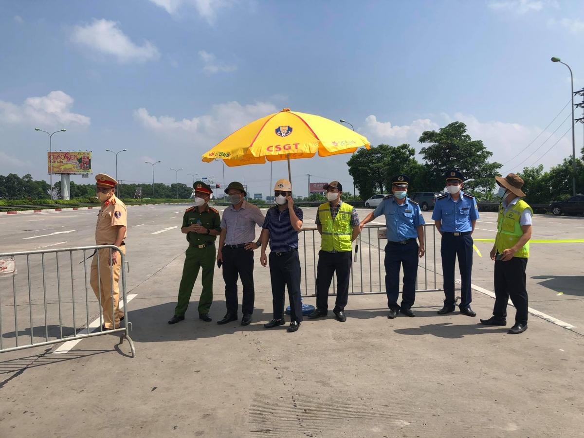 Ông Khuất Việt Hùng - Phó Chủ tịch chuyên trách Ủy ban ATGT Quốc trao đổi với các thành viên ban kiểm dịch tại trạm kiểm soát ở Hà Nội và ghi nhận tình hình ngày đầu Hà Nội thực hiện Chỉ thị 16.