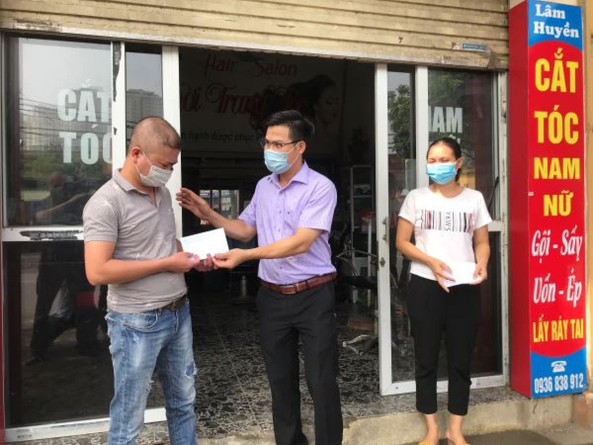 Lãnh đạo phường Kiến Hưng (quận Hà Đông) Nguyễn Duy Mạnh trao tiền hỗ trợ cho anh Trần Văn Lâm, Lê Thị Huyền là đối tượng lao động tự do