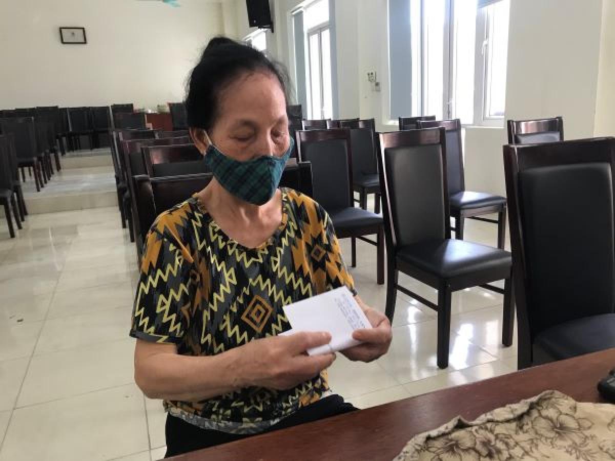Bà Trần Thị Loan thuộc hộ cận nghèo cẩn thận cất số tiền hỗ trợ vừa nhận được để mang về mua gạo cho gia đình.
