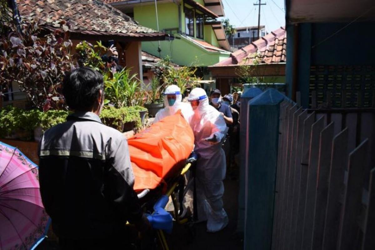 Các nhân viên y tế di chuyển thi thể nạn nhân mắc Covid-19 tử vong khi cách ly tại nhà ở Bandung, ngày 28/7/2021. Ảnh: AFP