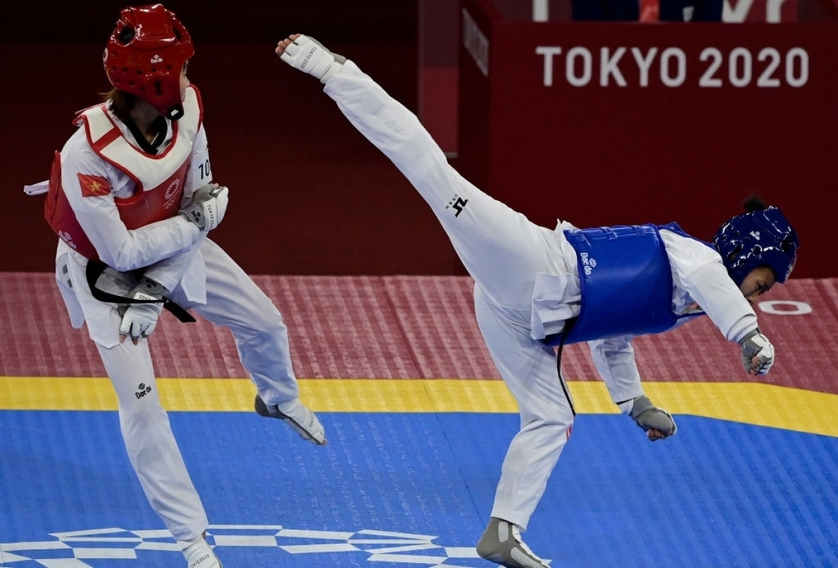 Kim Tuyen (in red gi) defeats Yvette Yong of Canada to enter the quarter-finals. (Photo: Getty)