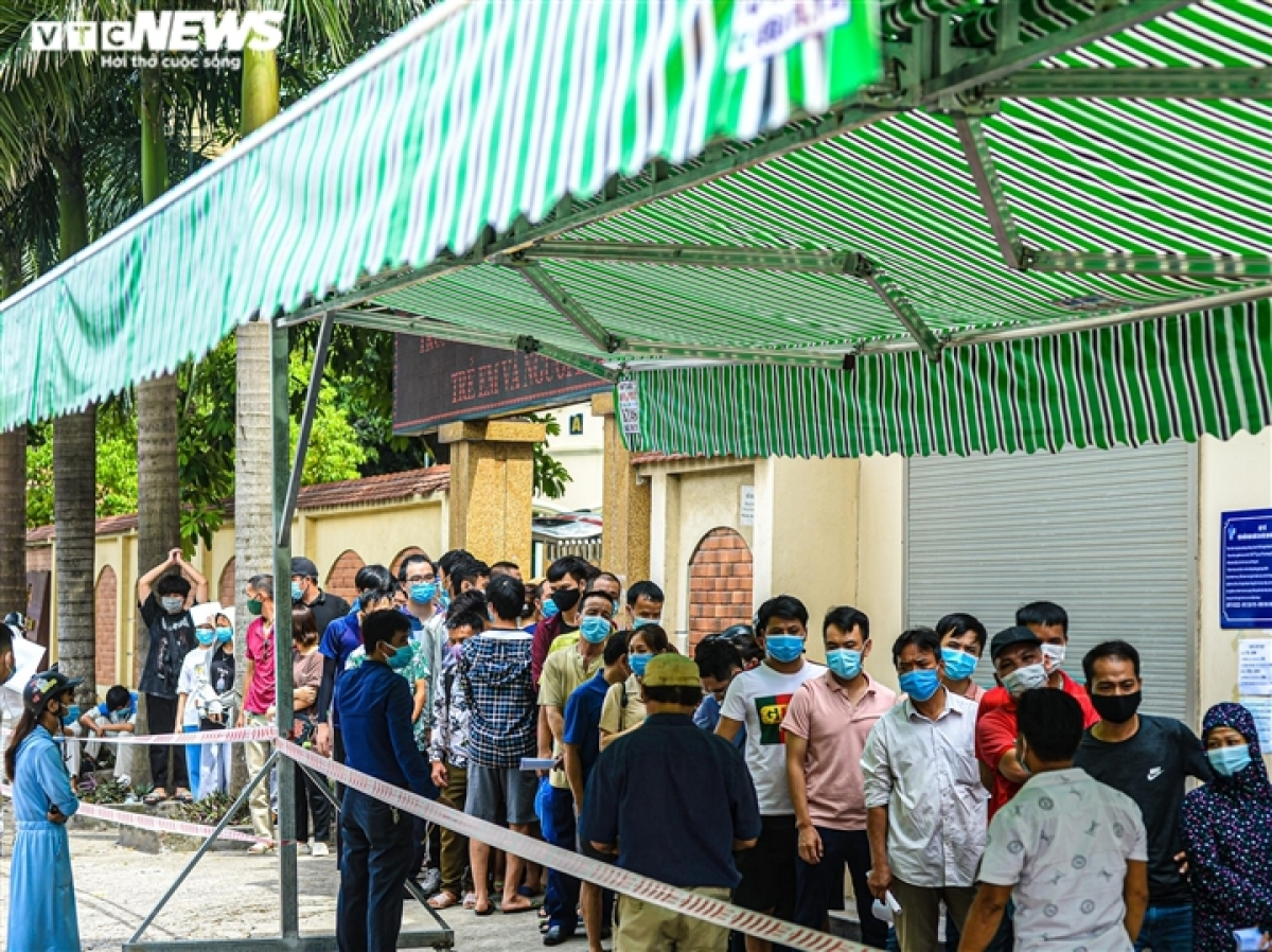A large number of local residents line up on Nghiem Xuan Yem street in Hoang Mai district from the early morning in order to undergo a COVID-19 test and get a certificate hours later, a document which is vital for them to travel from Hanoi to neighbouring localities.