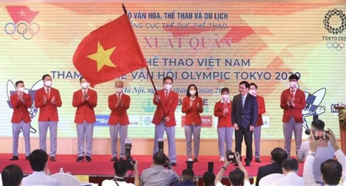 A member of the Vietnamese sports delegation holds the national flag handed over by Deputy Prime Minister Pham Binh Minh (front, right) at the send-off ceremony on July 13