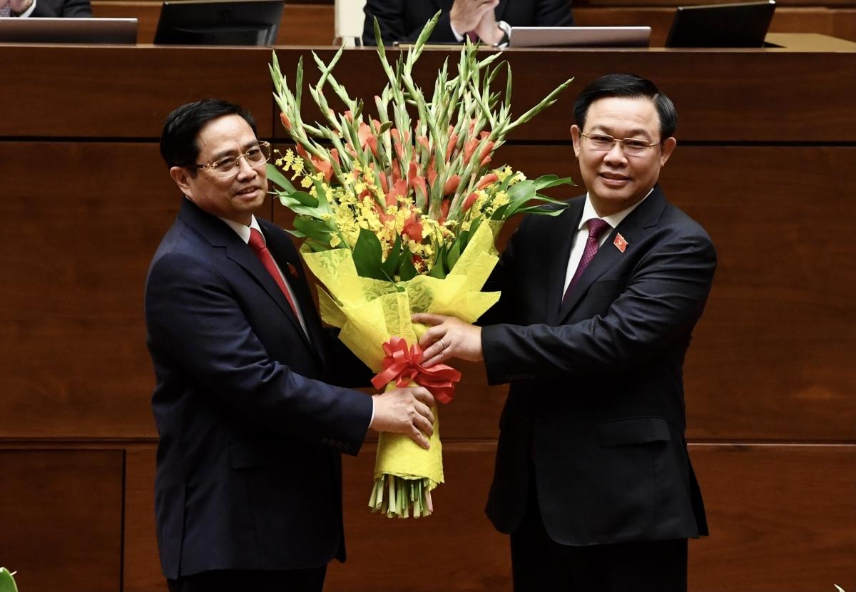 Thủ tướng Phạm Minh Chính nhận hoa từ Chủ tịch Quốc hội Vương Đình Huệ tại lễ tuyên thệ nhậm chức.