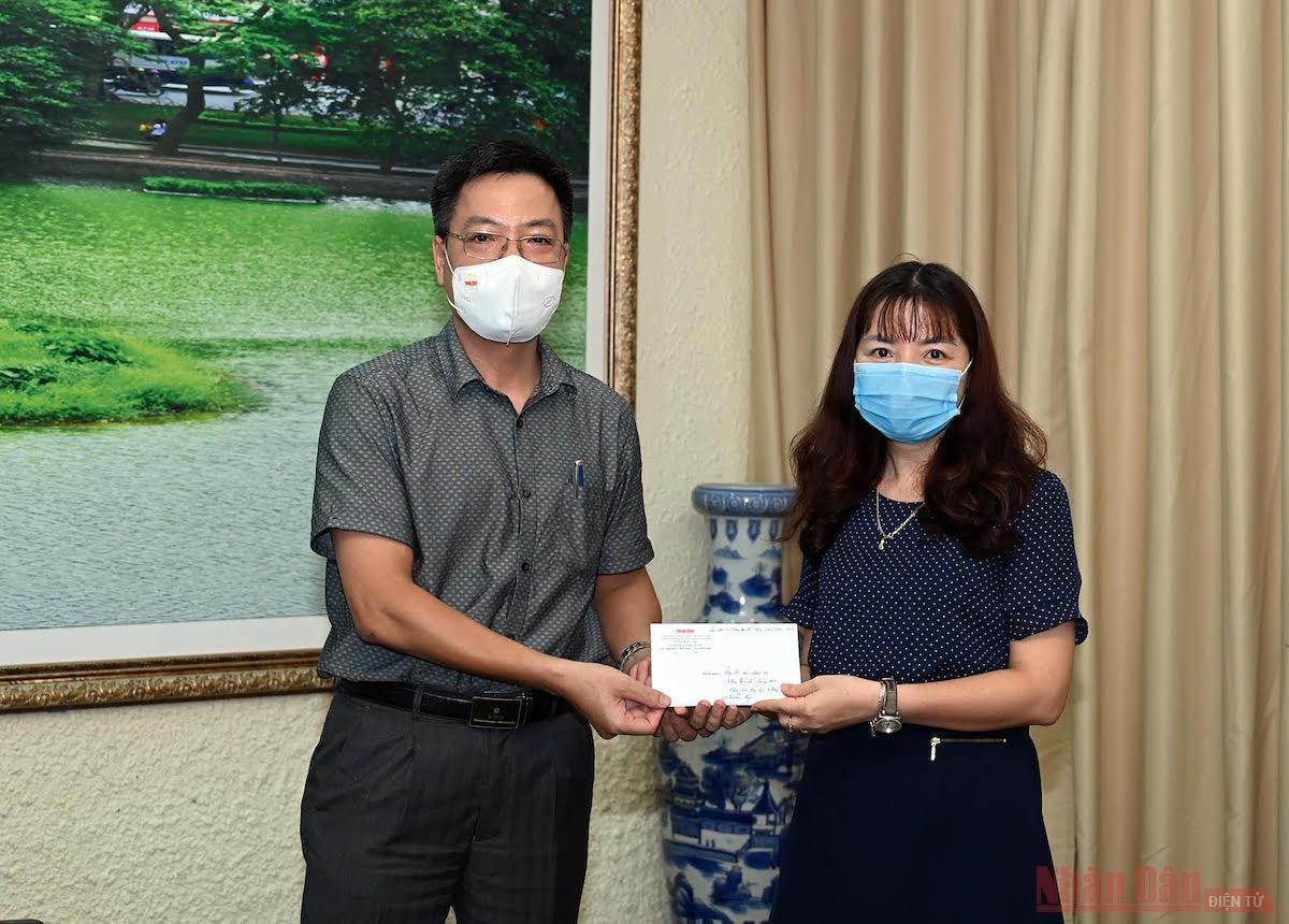 Ông Phan Huy Thắng, Trưởng Ban thư ký Biên tập Báo Nhân Dân trao quà hỗ trợ của các cựu sinh viên khoa Báo chí cho đại diện nhà trường.