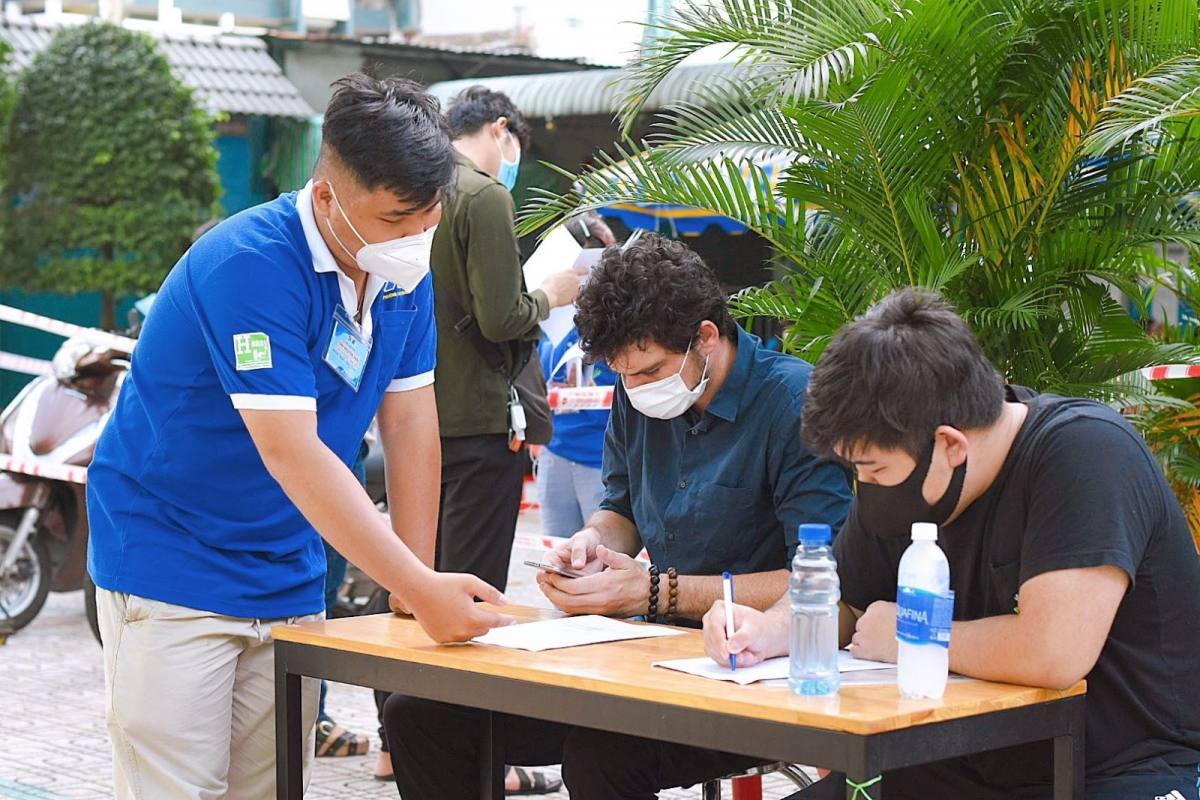 A volunteer in ward 1 of Tan Binh district instructs foreigners to fill in their healthcare declaration forms ahead of getting vaccinated against COVID-19.