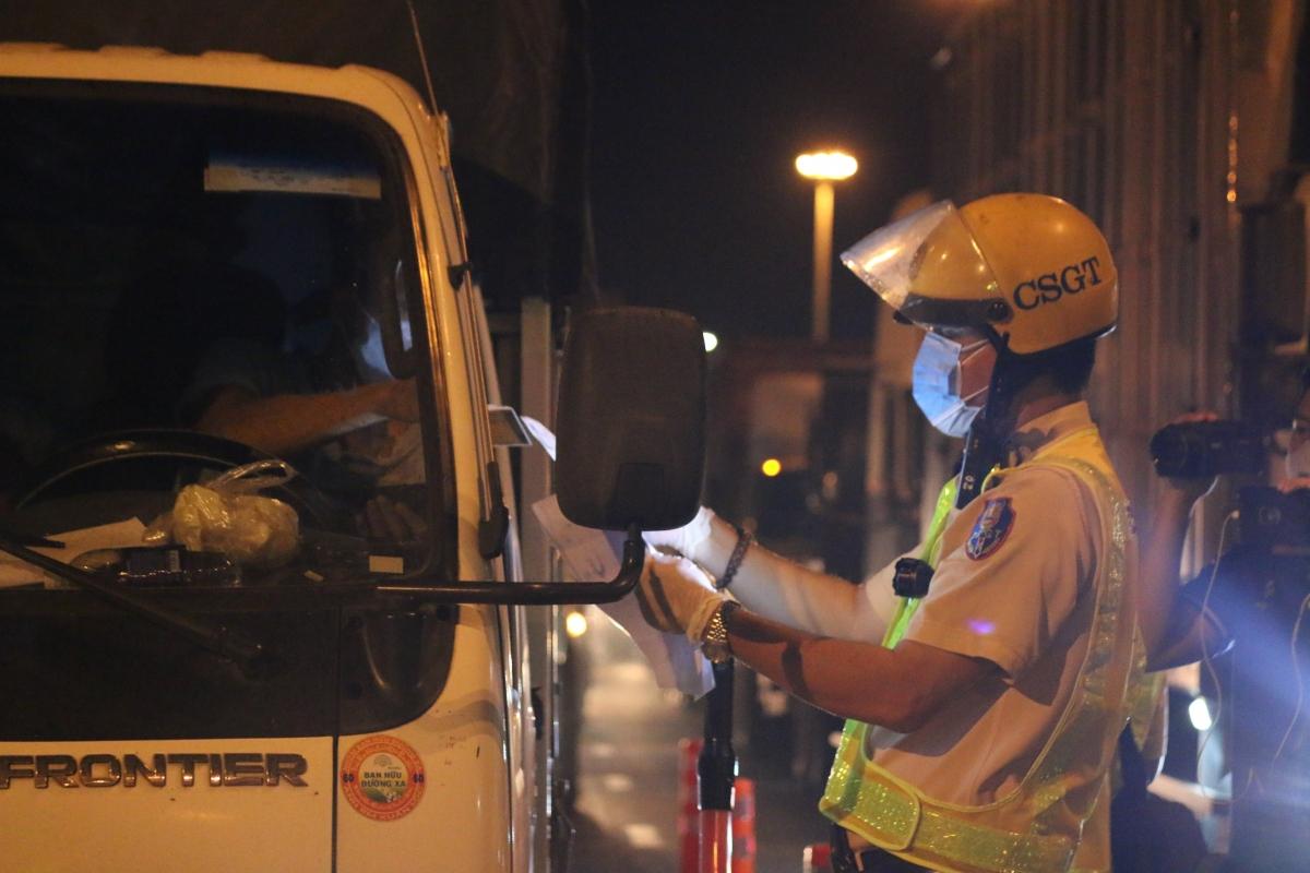 Chốt kiểm soát đang kiểm tra giấy tờ xe của vận chuyển hàng hóa qua chốt sau 18h.