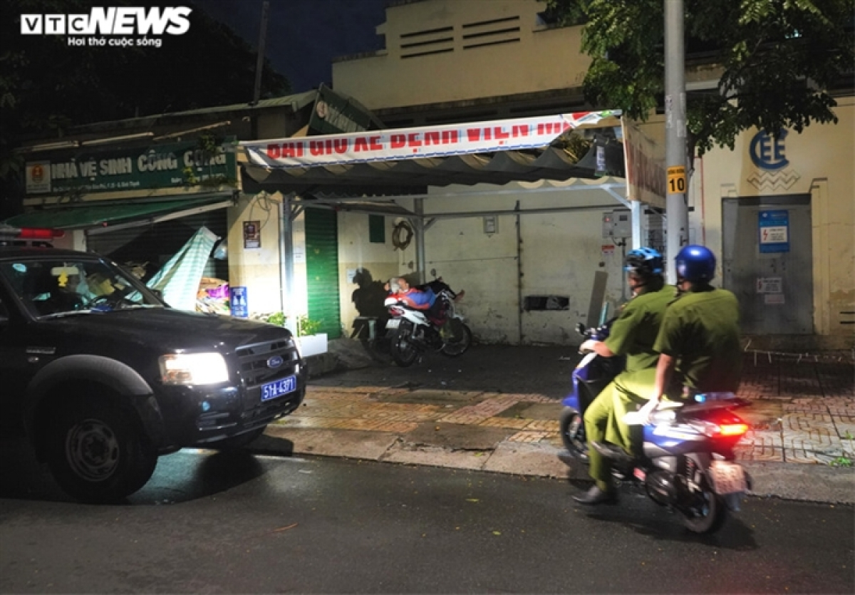 The police check on a man as he sleeps on a motorbike in Vo Thi Sau ward, District 3.