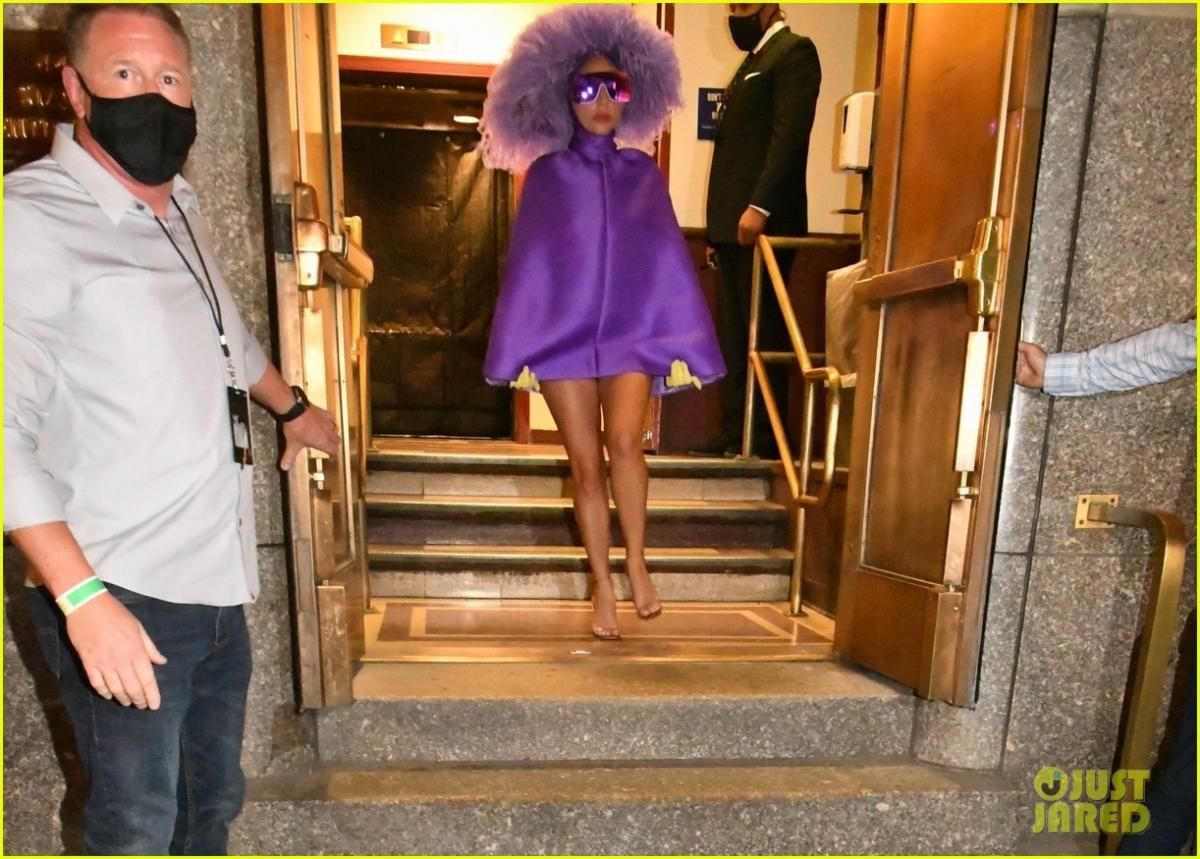 Nữ ca sĩ diện áo poncho màu tím của nhà thiết kế Pierpaolo Piccioli phối cùng mũ lông đà điểu của Philip Treacy.
