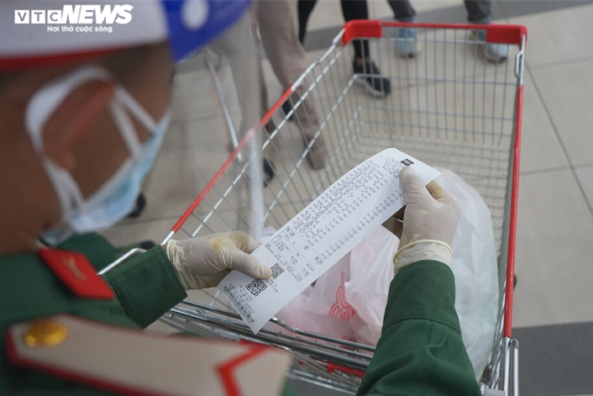 Military personnel check the list of goods before delivering them to residents.