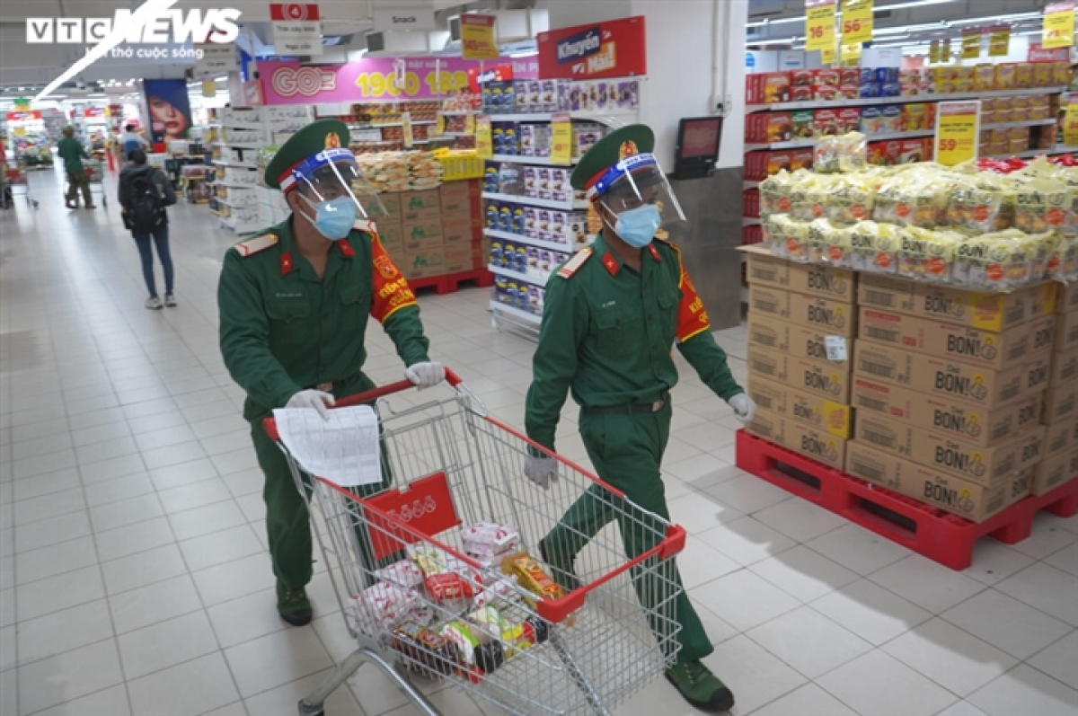 Many soldiers head to the supermarket in the early morning so they can buy essential food for residents in District 7.