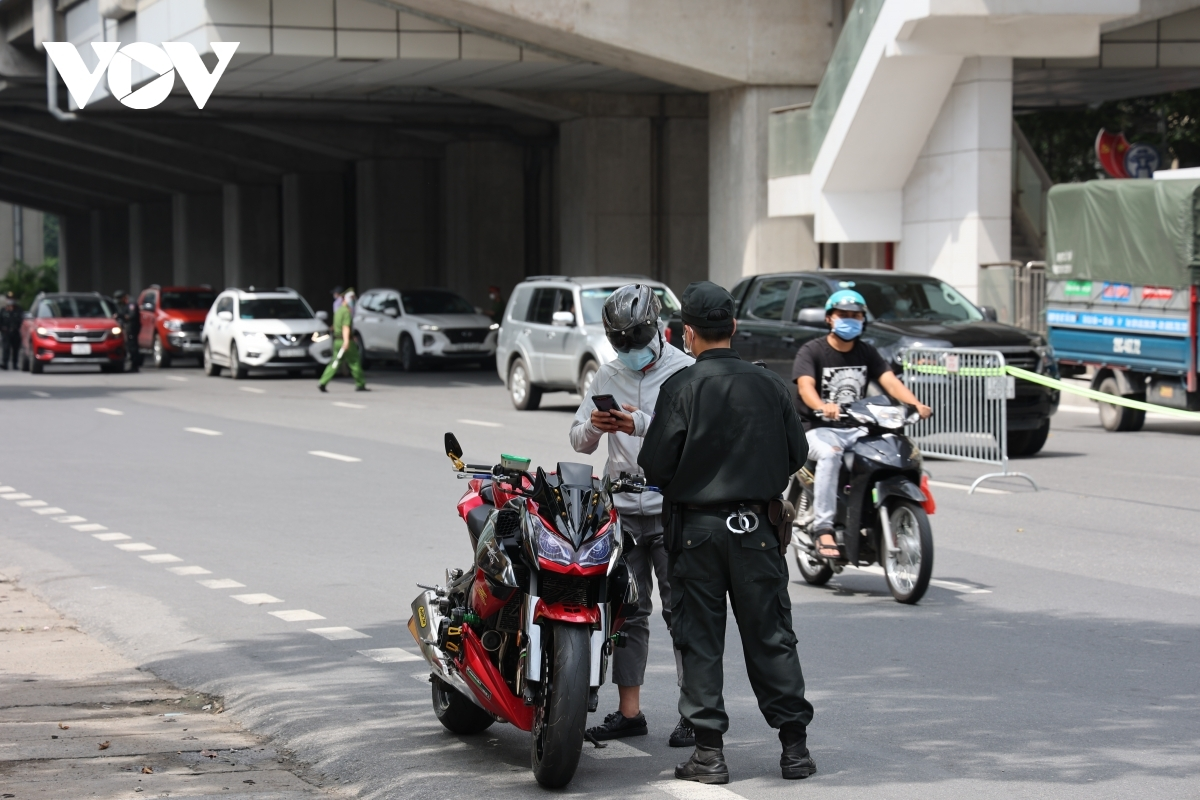 On-duty officials and residents maintain a safe distance at all times to curb the spread of the SARS-CoV-2 virus.