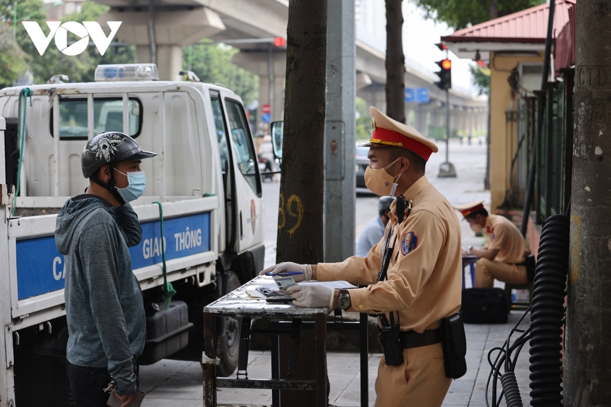 People who are outside without a valid reason are fined between VND1 million and VND3 million each at a checkpoint in Ha Dong district.