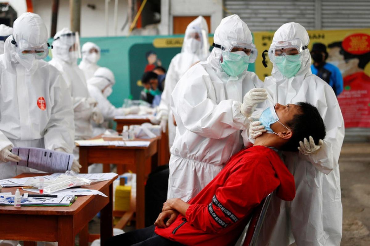 Nhân viên y tế lấy mẫu xét nghiệm Covid-19 gần thủ đô Jakarta, Indonesia. Ảnh: Reuters