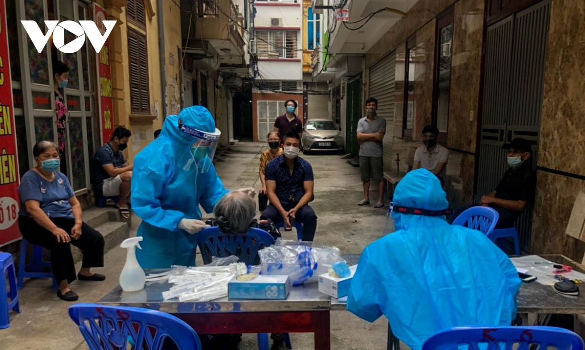 People come to get tested for COVID-19 and receive their first vaccine shot in Lieu Giai ward of Ba Dinh district.