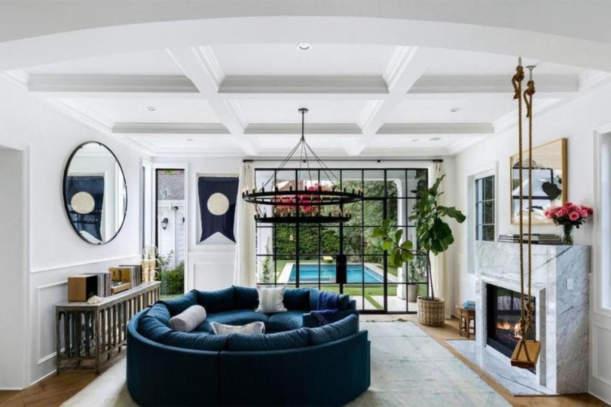 Phòng khách sang trọng với lò sưởi lát đá cẩm thạch và đèn chùm lấp lánh, nổi bật làchiếc ghế sofa tròn màu xanh đậm.