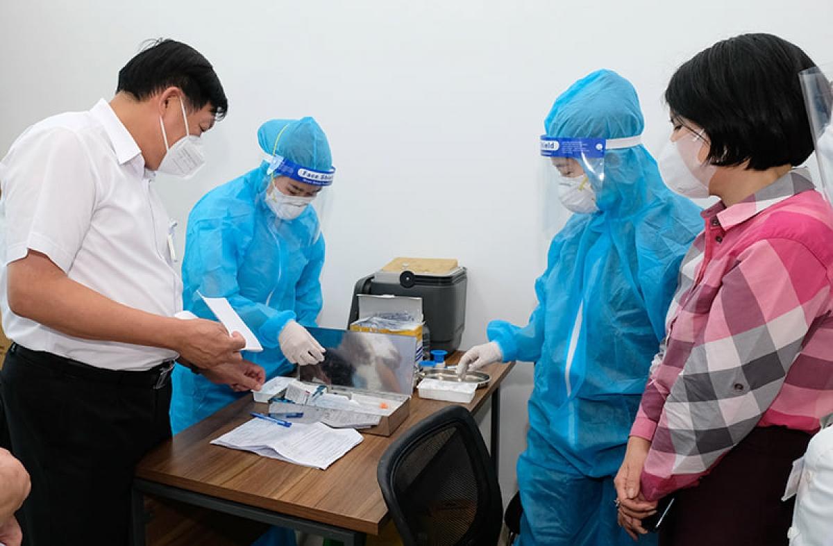 Thứ trưởng Bộ Y tế Đỗ Xuân Tuyên kiểm tra điểm tiêm chủng vaccine COVID-19 tại Hà Nội. (Ảnh: Trần Minh)