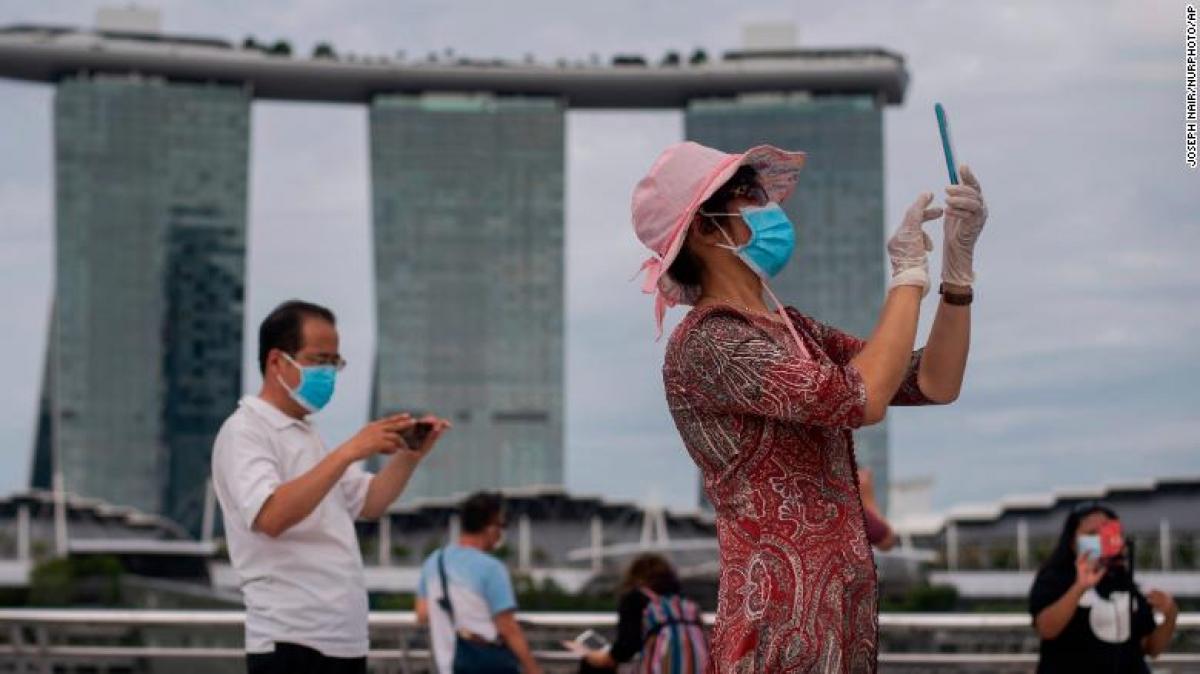Một người phụ nữ đeo khẩu trang và găng tay chụp hình ở Vịnh Marina, Singapore ngày 1/8. Ảnh: CNN