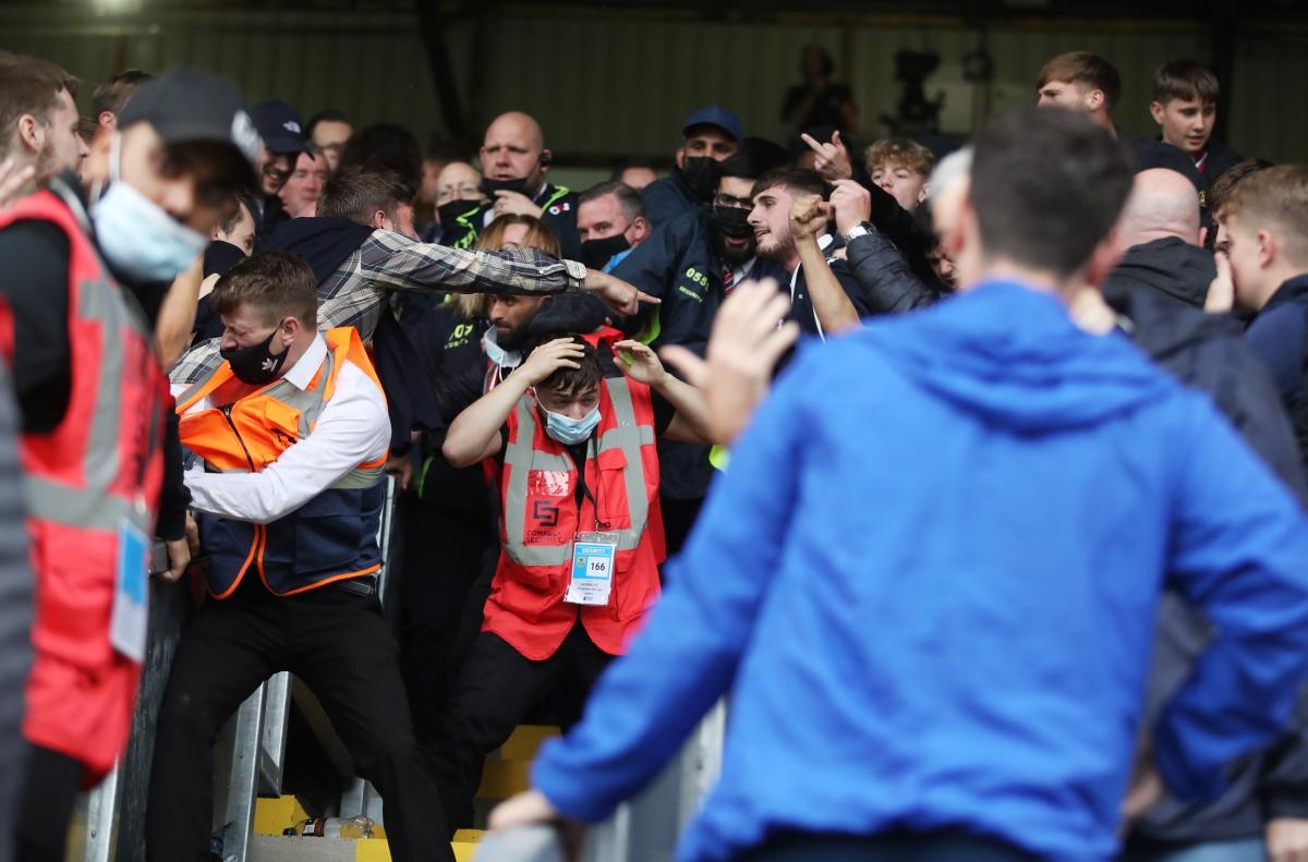 Hình ảnh một nhân viên sân đấuTurf Moor vất vả thoát khỏi đám đông hỗn loạn./.