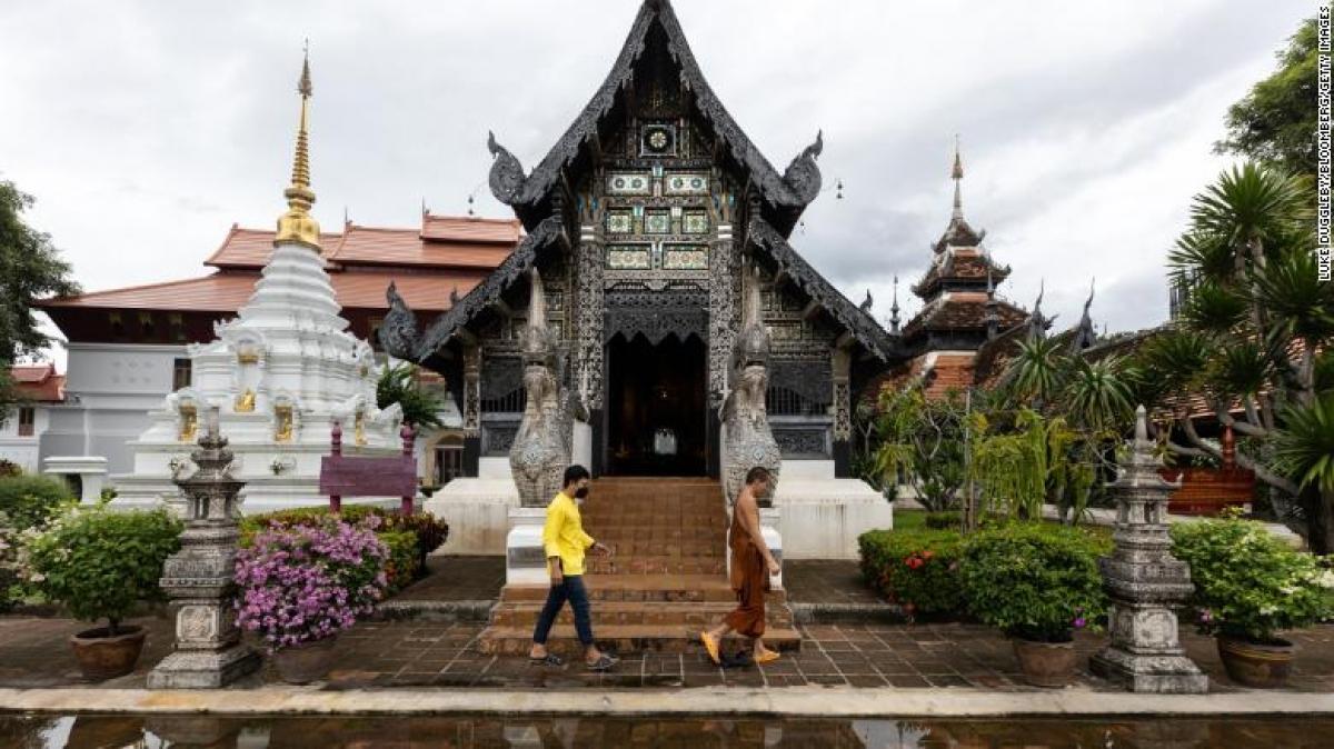 Một nhà sư đi bộ qua ngôi chùa Wat Chedi Luang ở Chiang Mai, Thái Lan ngày 3/9. Ảnh: CNN