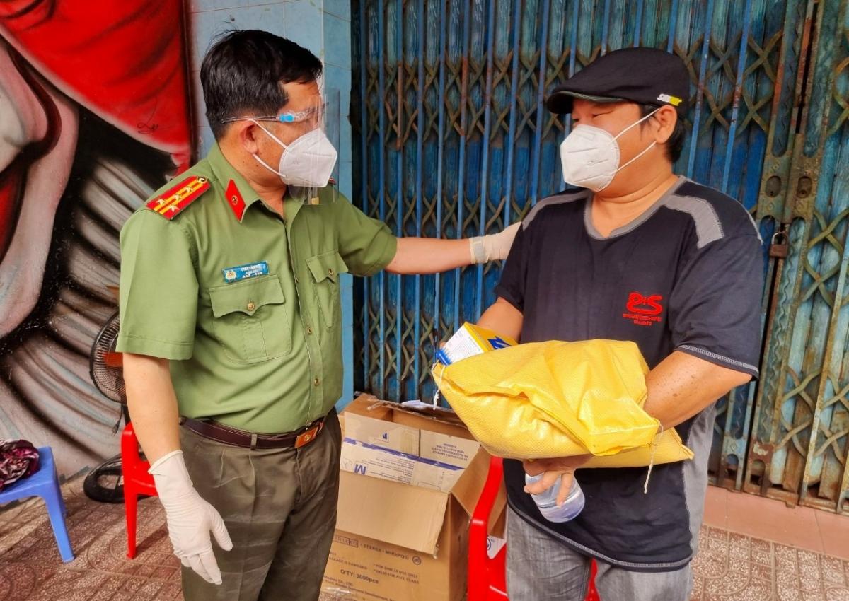 Đại tá Đinh Văn Nơi, Giám đốc Công an tỉnh tặng quà và ân cần dặn dò người dân khu phong tỏa thuộc thị trấn Phú Mỹ, huyện Phú Tân