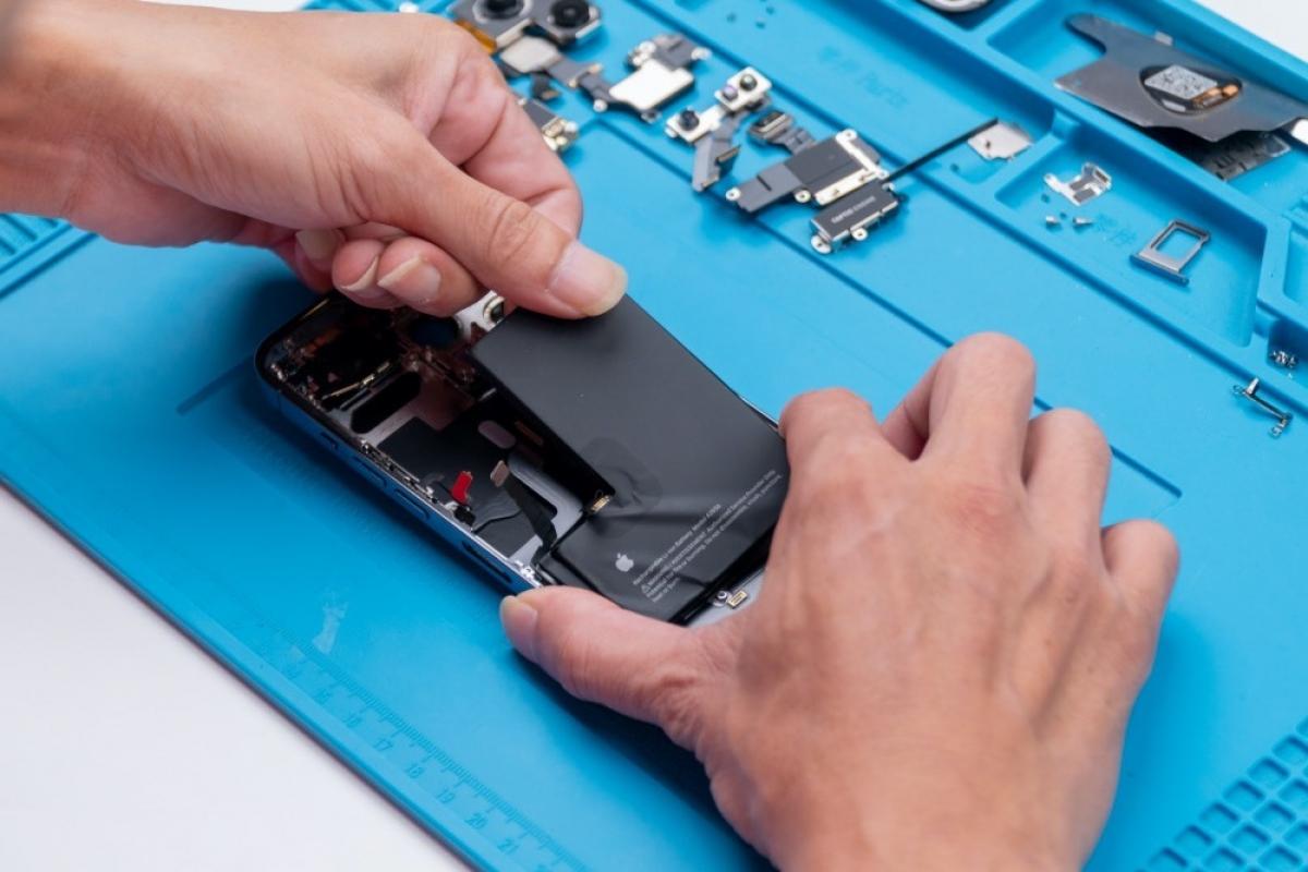 Kỹ thuật viên đang tiến hành tháo pin của iPhone 13 Pro