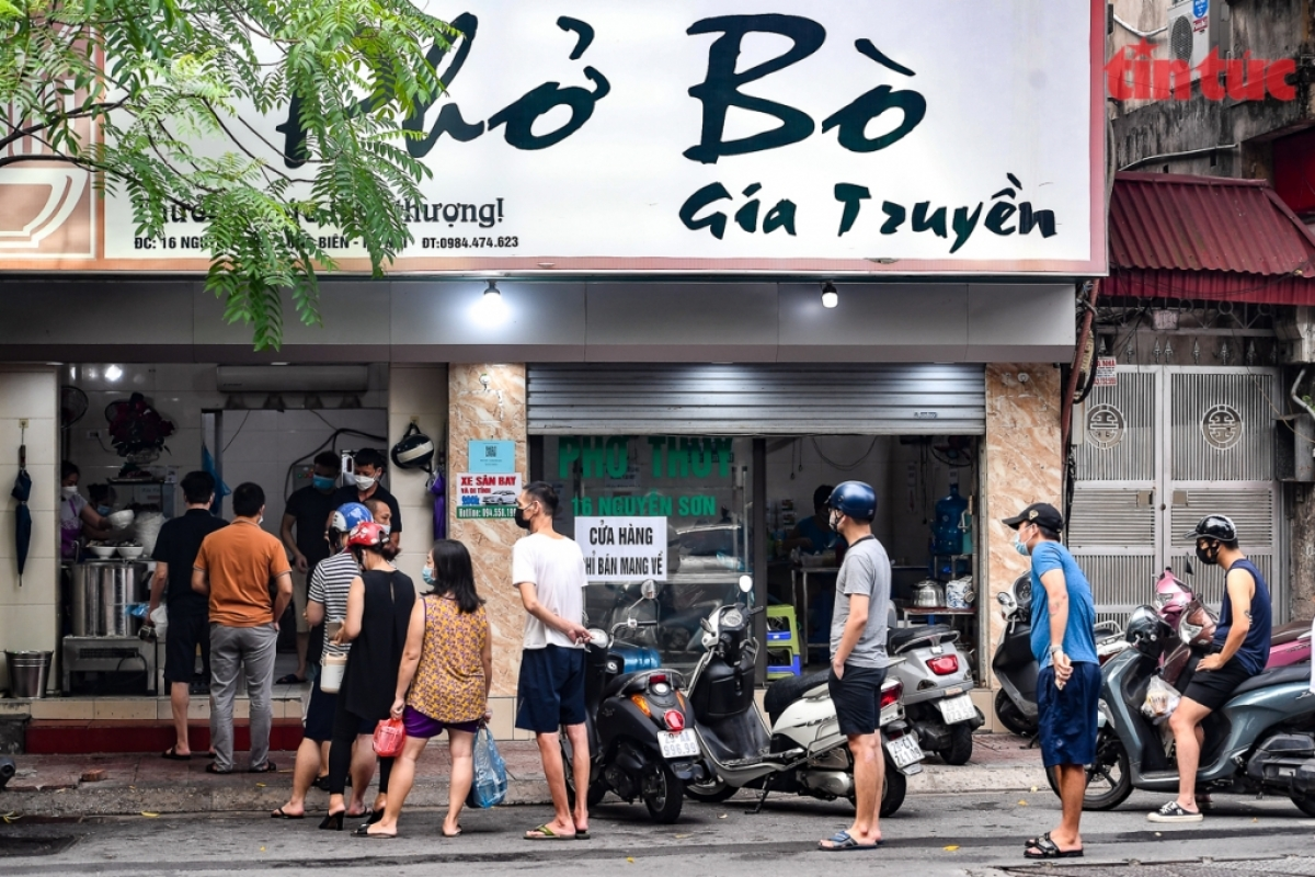 Local residents insafe areas queue up to buy Pho Bo (beefnoodlesoup)