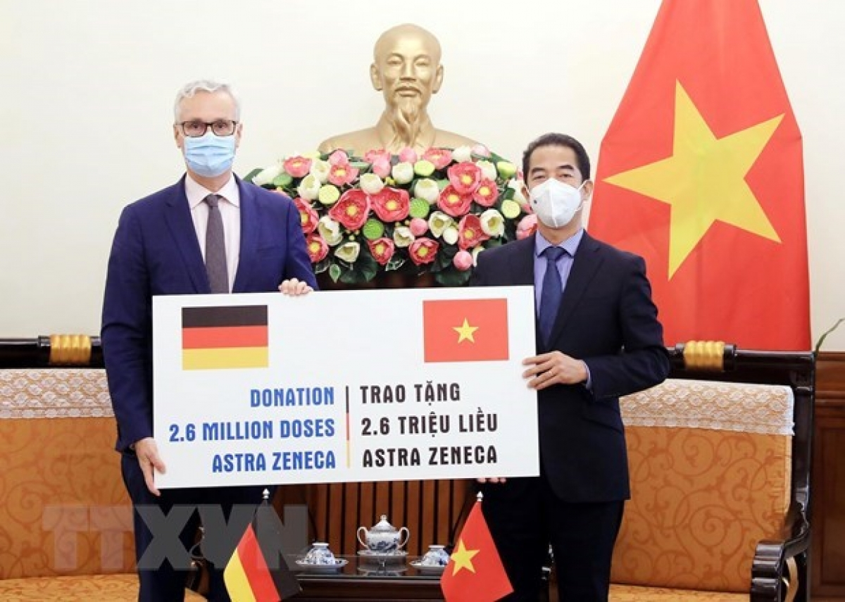 Deputy Minister of Foreign Affairs To Anh Dung (R) receives a token of the vaccine fromGerman Ambassador to Vietnam Guido Hildner at the ceremony (Photo: VNA)