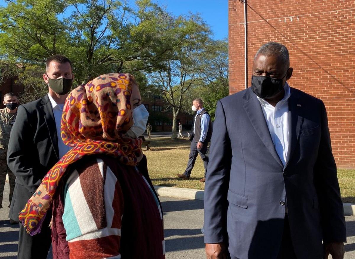 Bộ trưởng Quốc phòng Mỹ Lloyd Austin trò chuyện với một người phụ nữ Afghanistan trong chuyến thăm căn cứ McGuire-Dix-Lakehurst ngày 27/9. Ảnh: Reuters