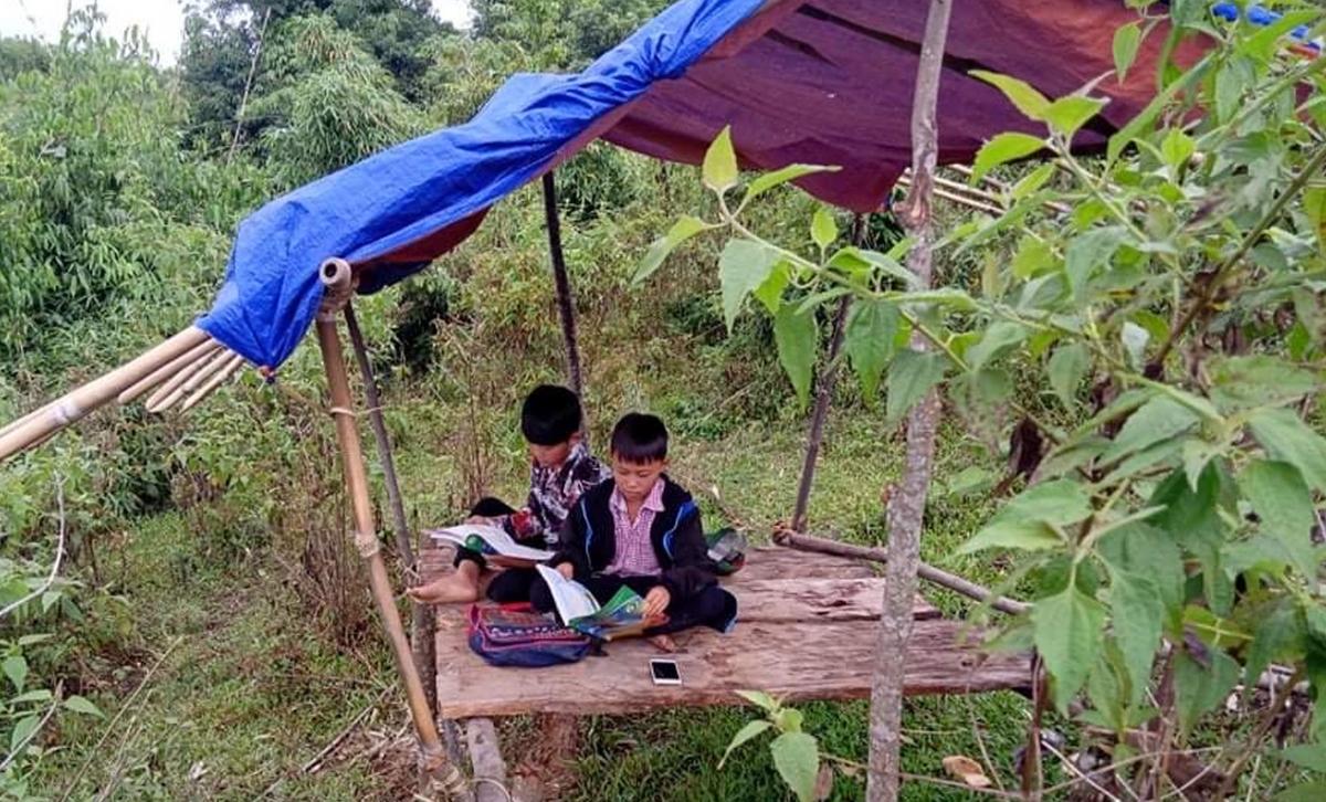 Hình ảnh hai cậu học sinh trong chiếc chòi đơn sơ học bài khiến thầy cô giáo xúc động. (Ảnh: CTV)